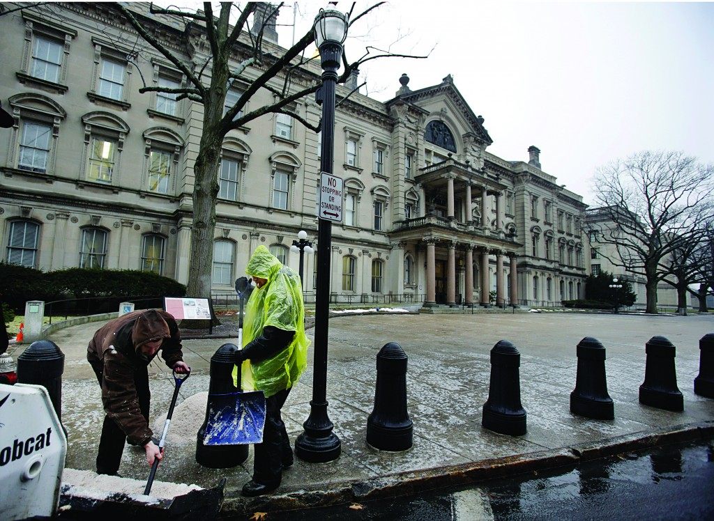 Workers salt icy sidewalks early Friday outside the Statehouse in Trenton, N.J. (AP Photo/Mel Evans)