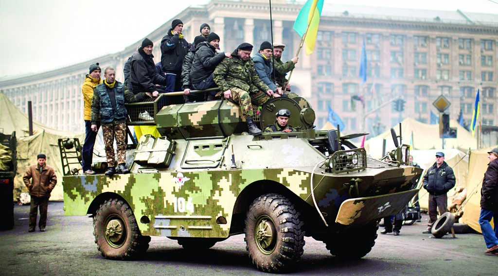 Anti-Yanukovych protesters riding on top of an army armored vehicle in Independence Square, the epicenter of the country's current unrest, in Kiev, Ukraine, Thursday. (AP Photo/Emilio Morenatti)