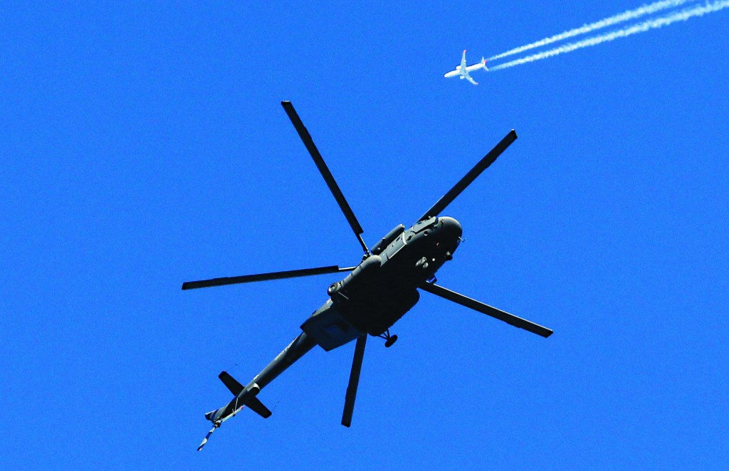 A military helicopter hovers over the mountain cluster as a passenger jet passes by prior to the 2014 Winter Olympics, which started Thursday, in Sochi, Russia.  (AP Photo/Dmitry Lovetsky)