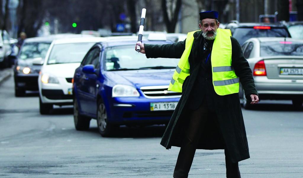An anti-Yanukovich protester regulates traffic in central Kiev Tuesday. (REUTERS/David Mdzinarishvili)