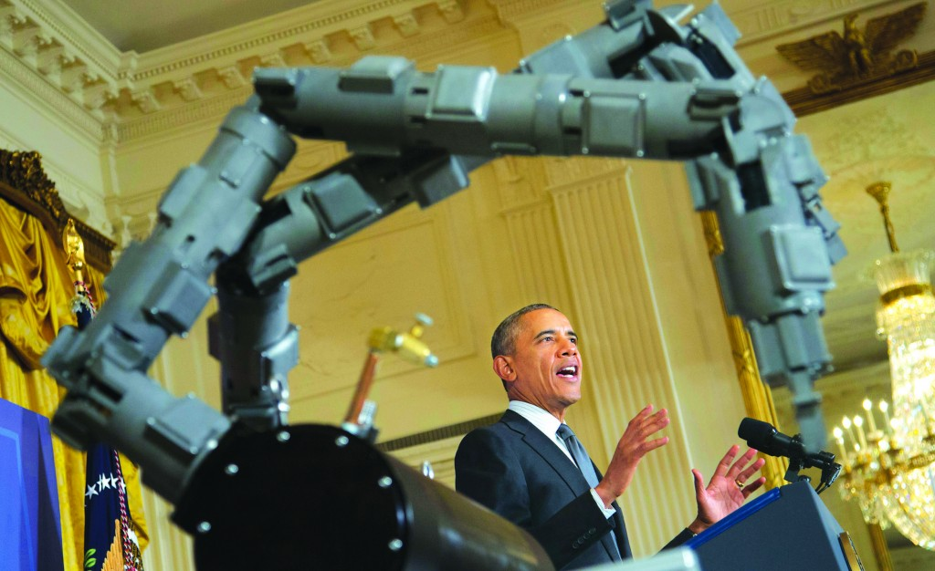 President Barack Obama stands next to a robotic arm, as he speaks about manufacturing innovation institutes, Tuesday, in the East Room of the White House in Washington. (AP Photo/Pablo Martinez Monsivais)