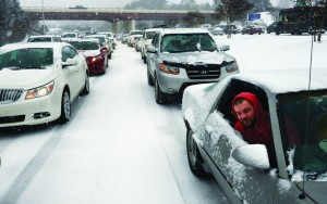 Kevin Miller looks out of the passenger window of his friend's car as they sit in stuck traffic during a winter storm Wednesday in Raleigh, N.C. (AP Photo/The News & Observer, Scott Sharpe)