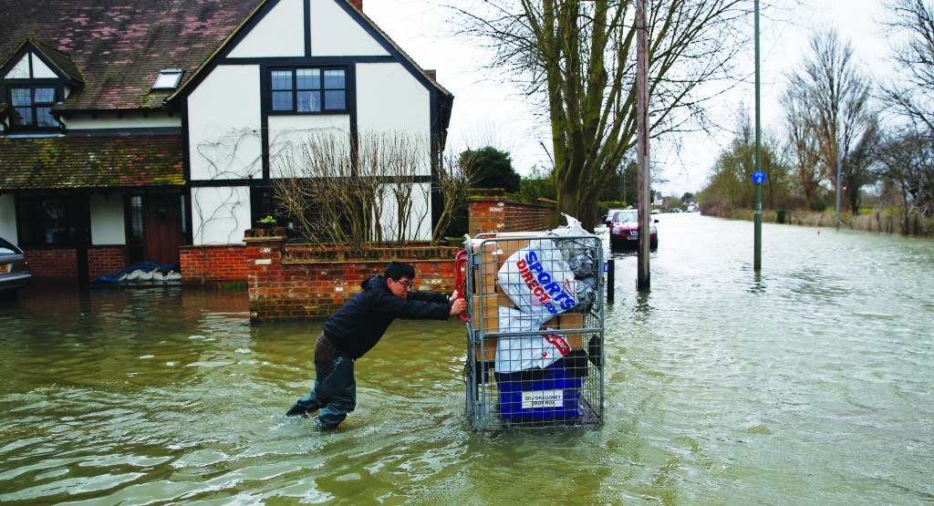 A local resident pushes belongings on a cart through the flooded part of the town of Staines-upon-Thames, England, as a police van patrols the area, Wednesday. (AP Photo/Lefteris Pitarakis)