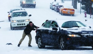 Robert Moss (L) and Isaac Granick (behind car) help Dan Schneider navigate his car up W. Hargett St. in the snow in Raleigh, N.C., Wednesday. (Ethan Hyman/Raleigh News & Observer/MCT)