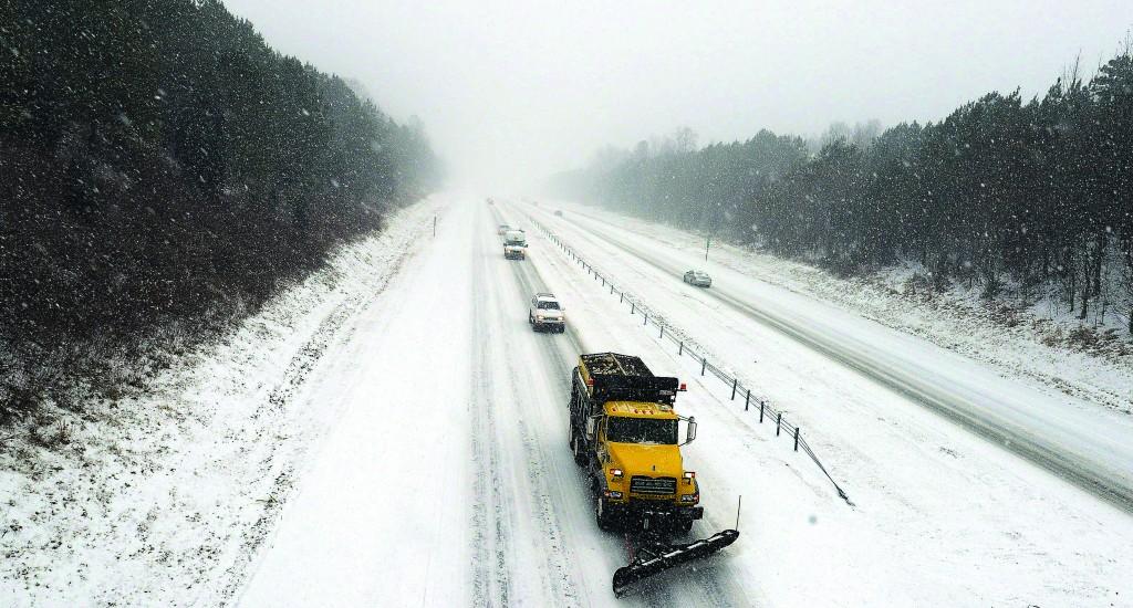 Vehicles travel west on Interstate 40 following a North Carolina Department of Transportation's snowplow on Wednesday, in Orange County, North Carolina. (AP Photo/The Herald-Sun, Bernard Thomas)
