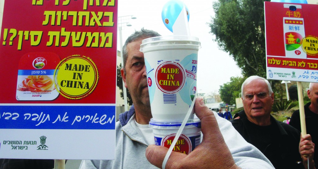 A protest was held against the pending sale of Tnuva to a Chinese company in front of the Apax offices in Tel Aviv on Monday.  (Roni Schutzer/Flash90)