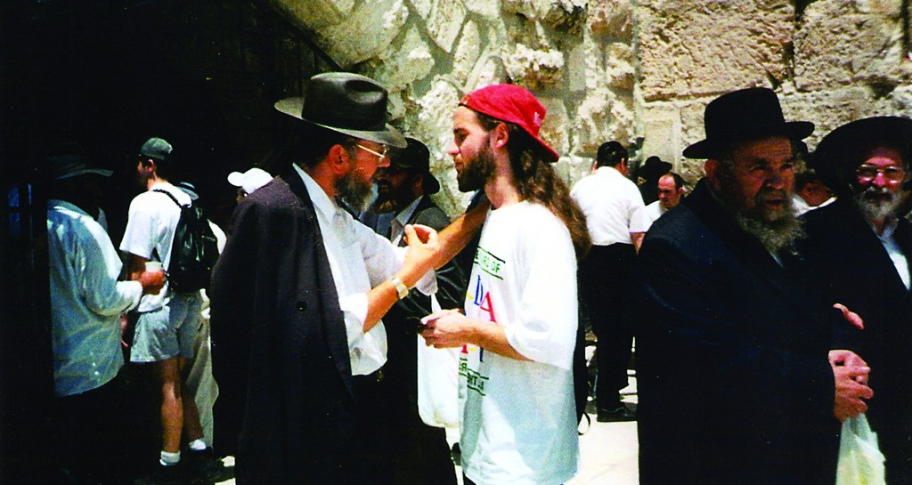 Rabbi Schuster conversing with a young Jewish man at the Kosel Plaza.