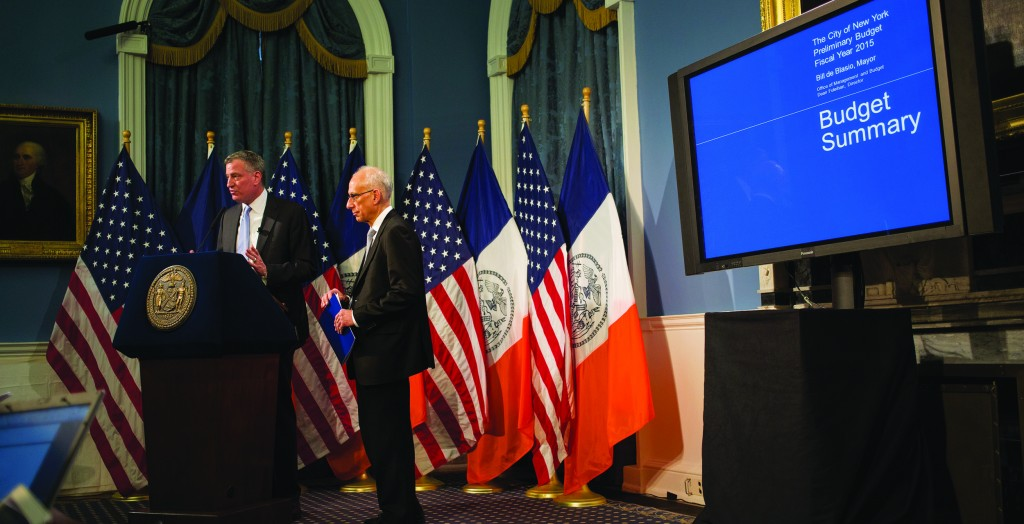 Mayor Bill de Blasio, standing with Budget Director Dean Fuleihan, delivers his budget address at City Hall, Wednesday. (AP Photo/Craig Ruttle)