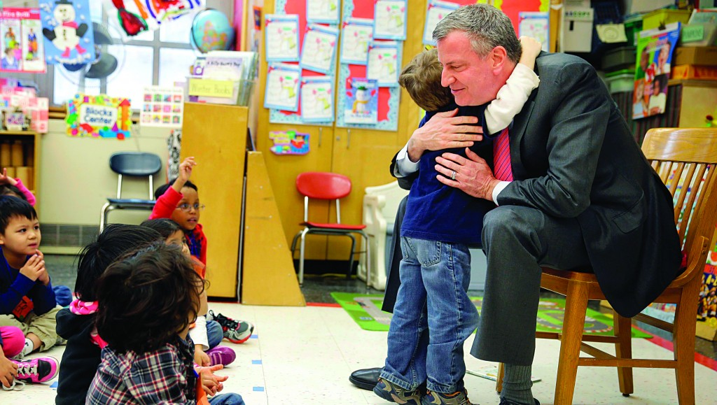 Mayor Bill de Blasio on Tuesday hugs a child after reading a book to a pre-kindergarten class in New York. (AP Photo/Seth Wenig)