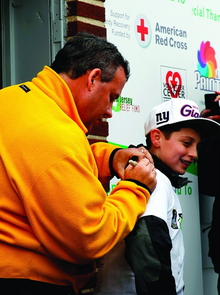 New Jersey Gov. Chris Christie on Friday autographs a shirt for Greg Blaze, 13. (AP Photo/Mel Evans)