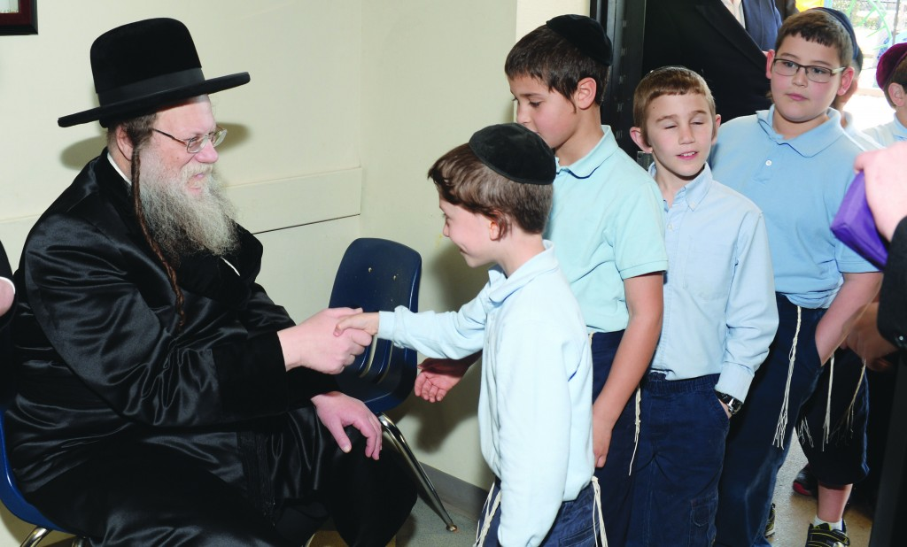 The Modzitzer Rebbe, shlita, giving brachos and copies of Megillas Esther to the talmidim of Torah Day School of Dallas on Erev Shabbos Vayakhel. See coverage on pages C12-C13. (Victor Dykman)