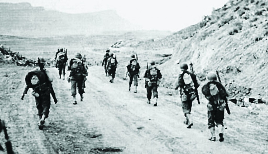 U.S. soldiers on the march during the Battle of Kasserine Pass.