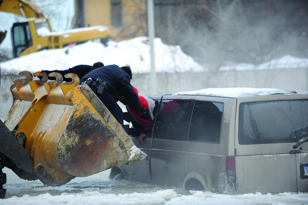 Detroit police use the scoop of a front-end loader to carry two people stranded in a minivan to safety after street flooding caused by a water main break on Friday, on Detroit's east side. Several vehicles were stuck in water and ice, prompting a rescue by police officers on construction equipment. (AP Photo/The Detroit New, David Coates)