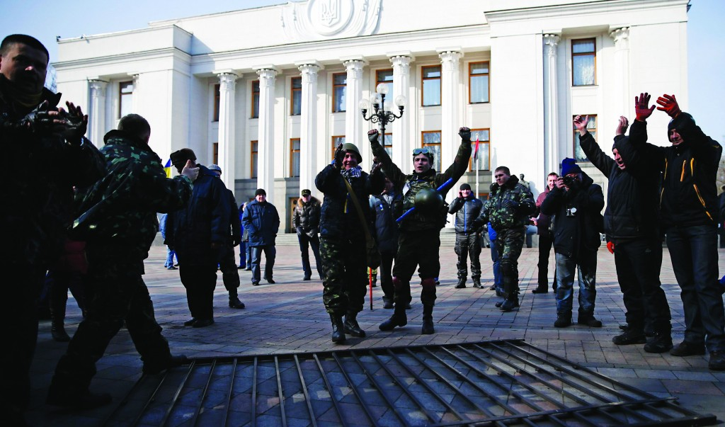 Members of self-defense units react after demolishing a fence enclosing the parliament building in Kiev, Wednesday. Ukraine's acting president, Oleksander Turchinov, has assumed the duties of head of the armed forces, the presidential website said on Wednesday. (REUTERS/David Mdzinarishvili)