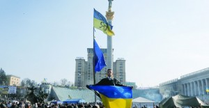 An anti-Yanukovych protester holds an Ukrainian flag in Kiev's Independence Square, Wednesday. (AP Photo/Efrem Lukatsky)