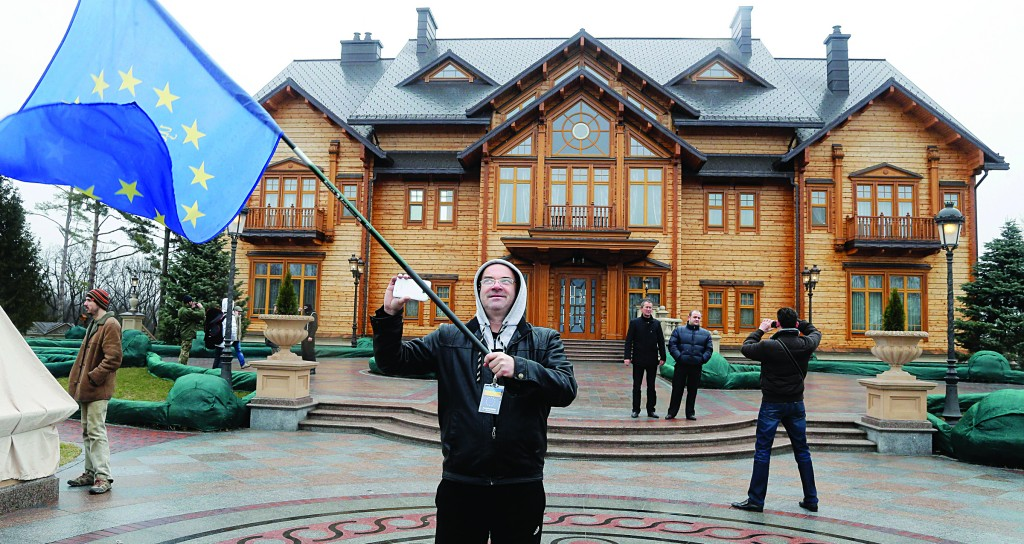 A protester waves an EU flag at the Ukrainian President Yanukovych's countryside residence in Mezhyhirya, Kiev's region, Ukraine, Saturday. Viktor Yanukovych is not in his official residence of Mezhyhirya, which is about 20 kilometres north of the capital. (AP Photo/Efrem Lukatsky)