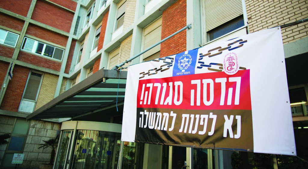 """Yerushalayim's Hadassah Ein-Kerem Hospital on Tuesday. The sign reads: """"Hadassah is Closed. Please contact the government."""" (Yonatan Sindel/Flash90)"""