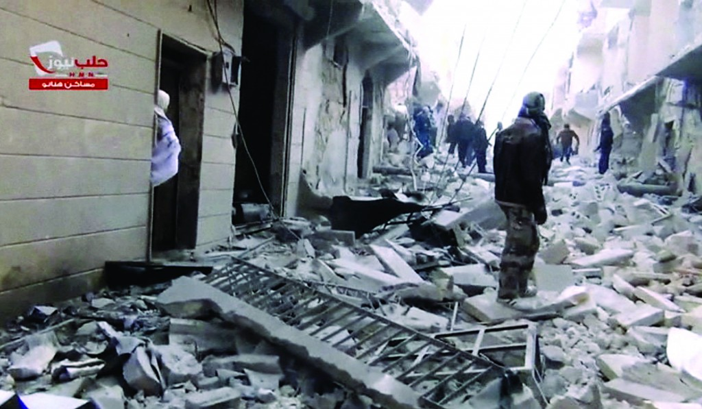 People walk on a street covered with the rubble of damaged buildings after activists said a barrel bomb was dropped in Aleppo, Syria, Thursday, Feb. 6. Syrian rebels launched a new push in Aleppo on Thursday to capture key symbols of the government, storming a prison there, freeing hundreds of prisoners. (AP Photo/Aleppo News Network)