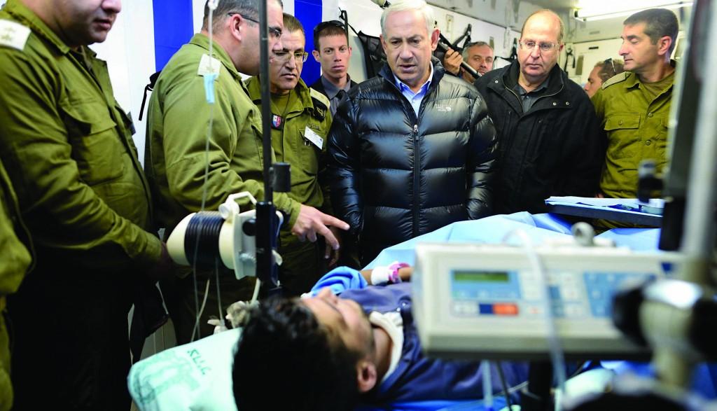 Israeli Prime Minister Binyamin Netanyahu visiting victims of the Syrian civil war at an IDF field hospital in the Golan on Tuesday.  (Kobi Gideon /GPO/FLASH90)