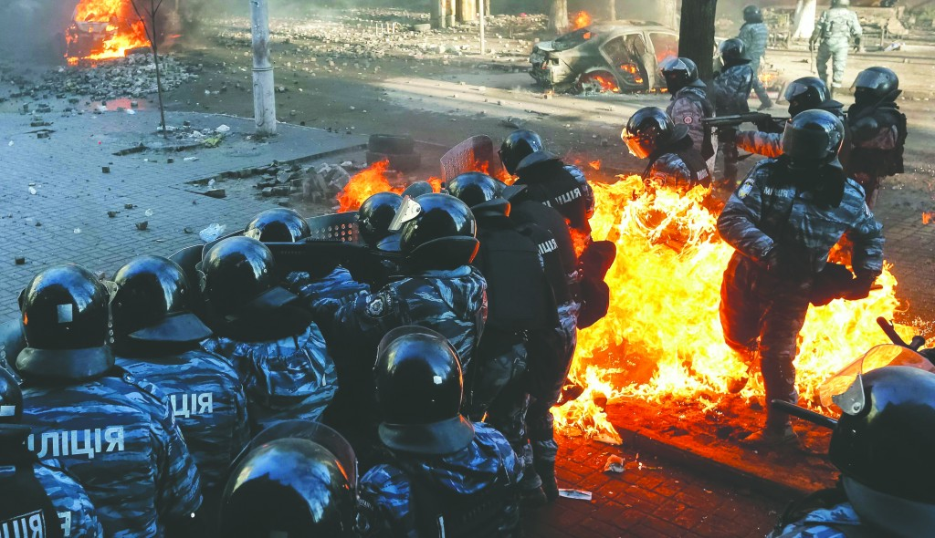 Riot policemen stand guard as they are hit by fire caused by Molotov cocktails hurled by anti-government protesters during clashes in Kiev Tuesday. (REUTERS/Stringer)