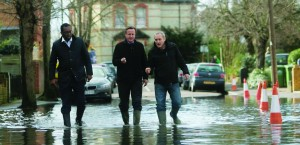 Britain's Prime Minister David Cameron (C) speaks with resident Ray Connerlley (R) and Kwasi Kwarteng, the MP for Spelthorne, as they walk through flood water in Guildford Street in Staines-upon-Thames, southwest of London on February 11, 2014. (REUTERS/Steve Parsons/pool)