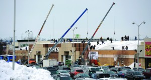 Work crews remove snow from the roof of a Kohl's in Woodland Park, N.J., Sunday. (AP Photo/Northjersey.com, Tyson Trish)