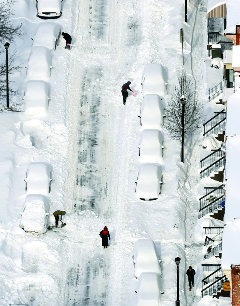 Man on Friday digs out a vehicle buried in snow in downtown Albany. (AP Photo/Mark Lennihan)