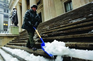 U.S. Parks Service employee Danny Merced on Wednesday clears snow from the steps of Federal Hall in New York's Financial District. (AP Photo/Richard Drew)
