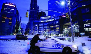 A New York City police officer on Friday scrapes snow from his patrol car. (AP Photo/Mark Lennihan)