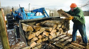 Devillo Peck loads firewood in the back of his tractor in Milford, N.Y., on Monday to prepare for the possibility of a snowstorm this week. (AP Photo/The Daily Star, Benjamin Patton)