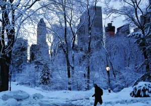 A man walks on Friday between snow drifts in Central Park. (AP Photo/John Minchillo)