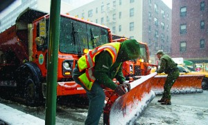 Sanitation workers adjust plows during a snowstorm Monday.  (Rob Bennett/Office of the Mayor)