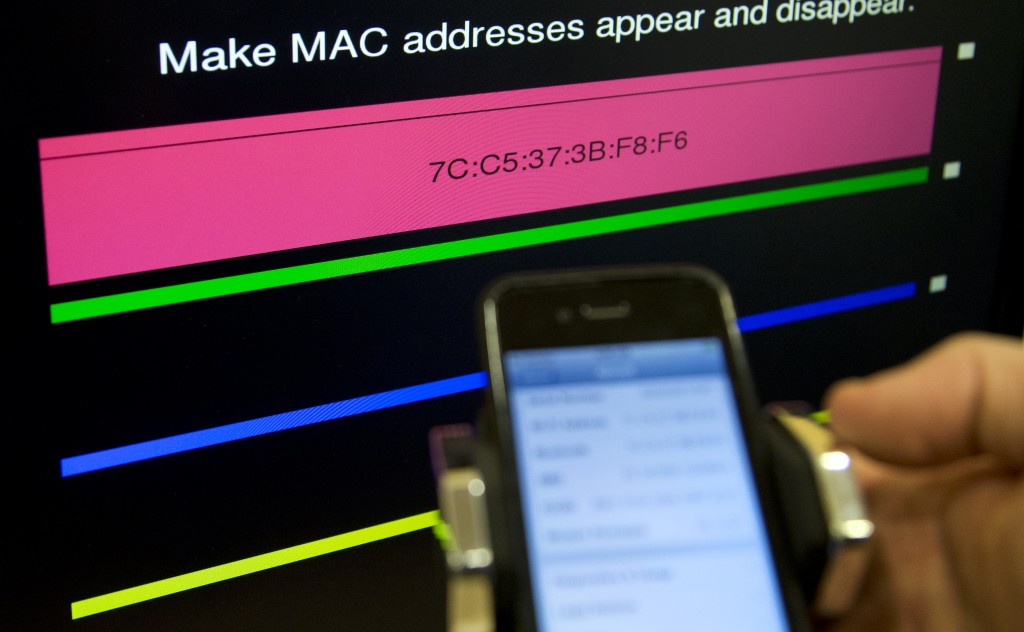 Technologist Seth Schoen holds a cellphone as it displays information, also seen on the screen behind, during a Federal Trade Commission (FTC) mobile tracking demonstration, Wednesday, Feb. 19, 2014, in Washington. (AP Photo/Carolyn Kaster)