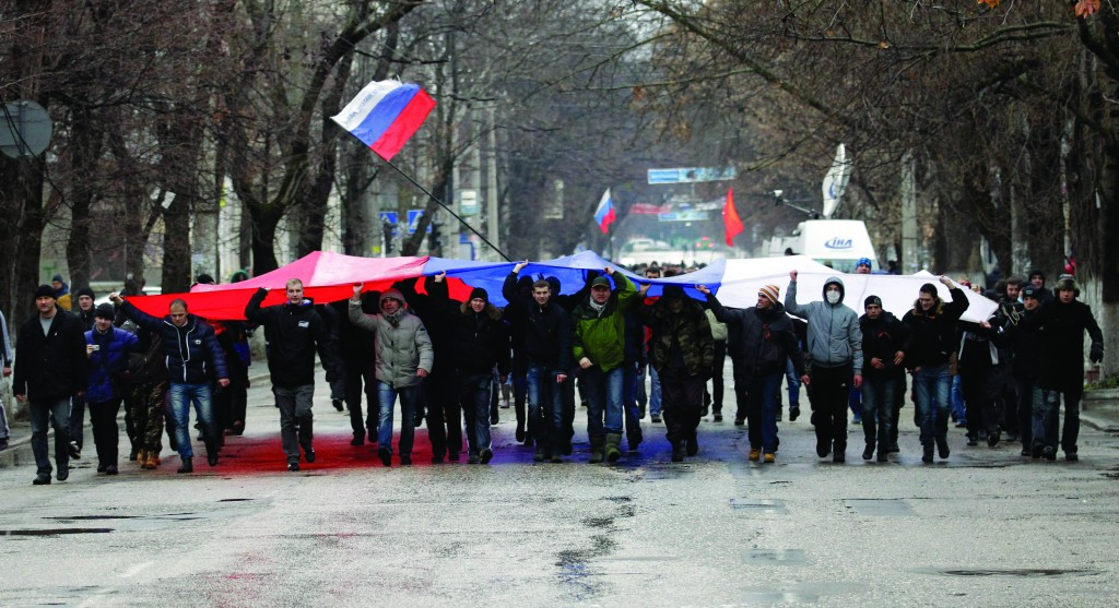 Pro-Russian demonstrators march with a huge Russian flag during a protest in front of a local government building in Simferopol, Crimea, Ukraine, Thursday, Feb. 27, 2014.  (AP Photo/Darko Vojinovic)