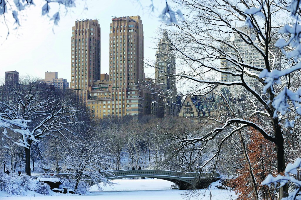 People walk through a snow-covered Central Park in New York, Tuesday, Feb. 4, 2014. Just as the East Coast dug out from a canopy of wet, heavy snow that again shut schools and emptied workplaces, another hit was expected to sock the Midwest.  (AP Photo/Seth Wenig)