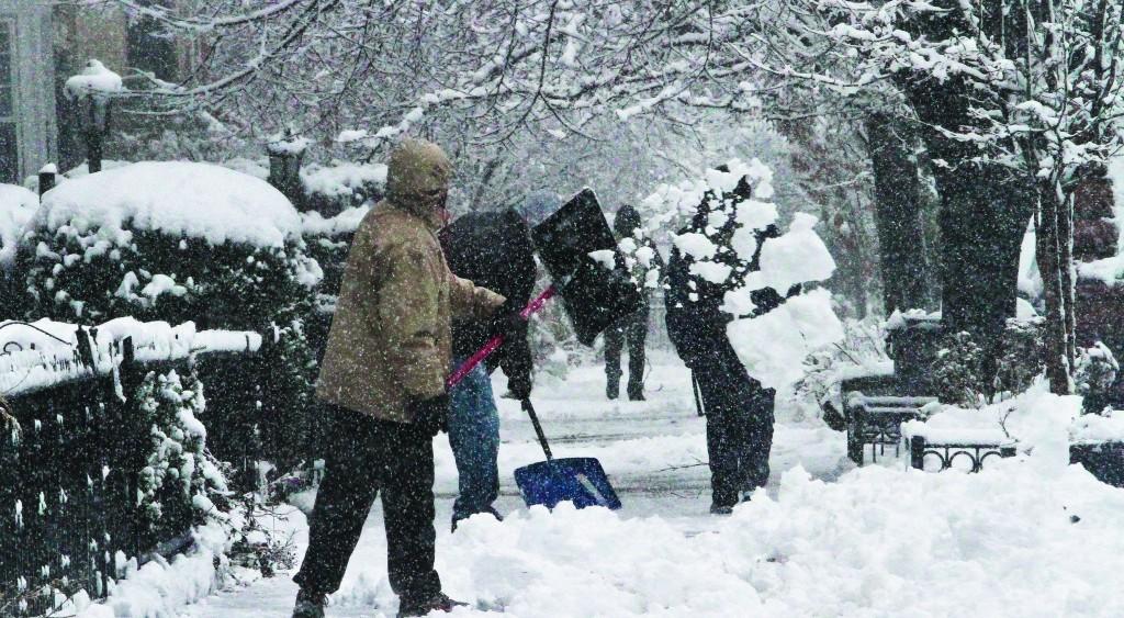 Shovelers remove snow from a sidewalk in Brooklyn's Flatbush neighborhood on Monday Feb. 3, 2014, in New York. (AP Photo/Bebeto Matthews)