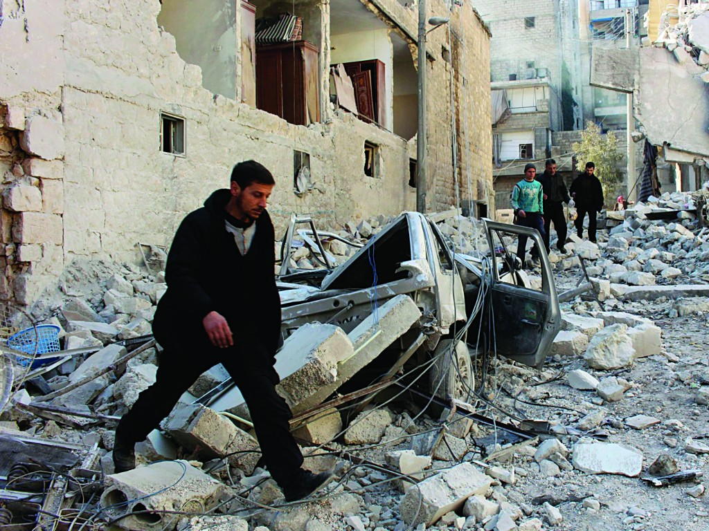 Men inspect a site hit by what activists said was an airstrike by forces loyal to Syria's President Bashar al-Assad in the al-Sukkari neighbourhood in Aleppo Tuesday.  Bombings by Syrian forces killed at least seven people Tuesday. (REUTERS/Mahmoud Hebbo)