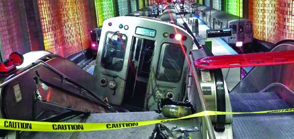 A Chicago Transit Authority train car rests on an escalator at the O'Hare Airport station after it derailed early Monday. (AP Photo/NBC Chicago, Kenneth Webster)