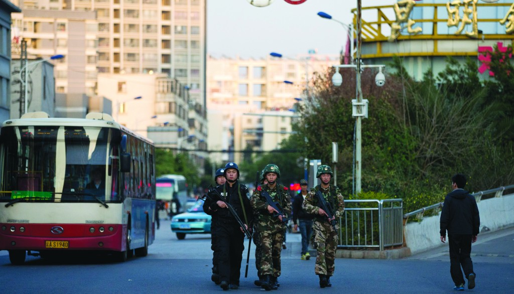 Armed policemen and paramilitary policemen patrol a street near the Kunming Railway Station, where more than 10 assailants slashed scores of people with knives Saturday evening, in Kunming, in southwestern China's Yunnan province, Monday. (AP Photo/Alexander F. Yuan)