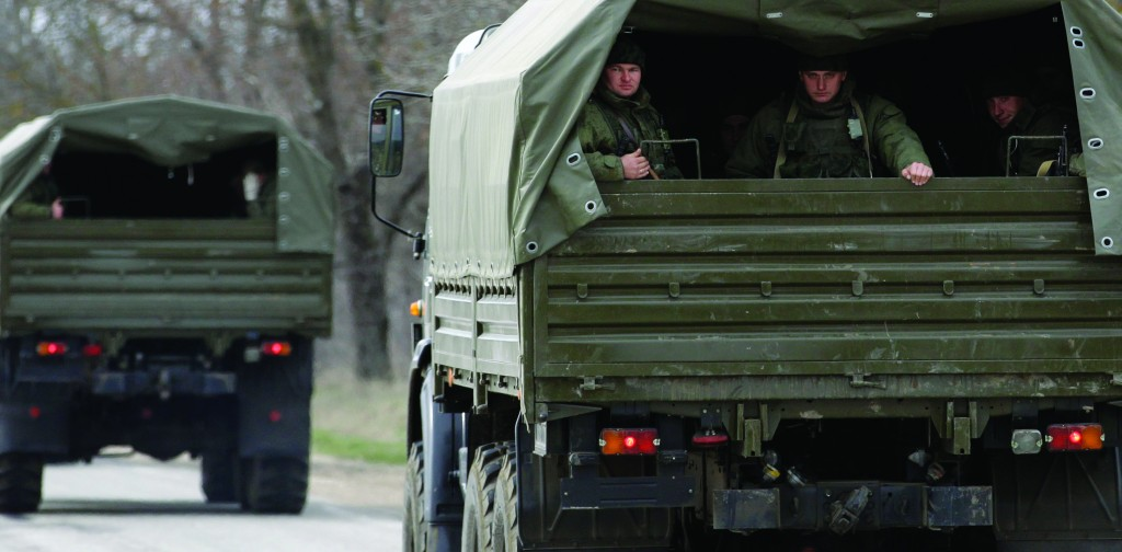 Uniformed men look out of military vehicles bearing no license plates as they travel on the road from Feodosia to Simferopol in the Crimea, Ukraine, Saturday.  (AP Photo/Darko Vojinovic)