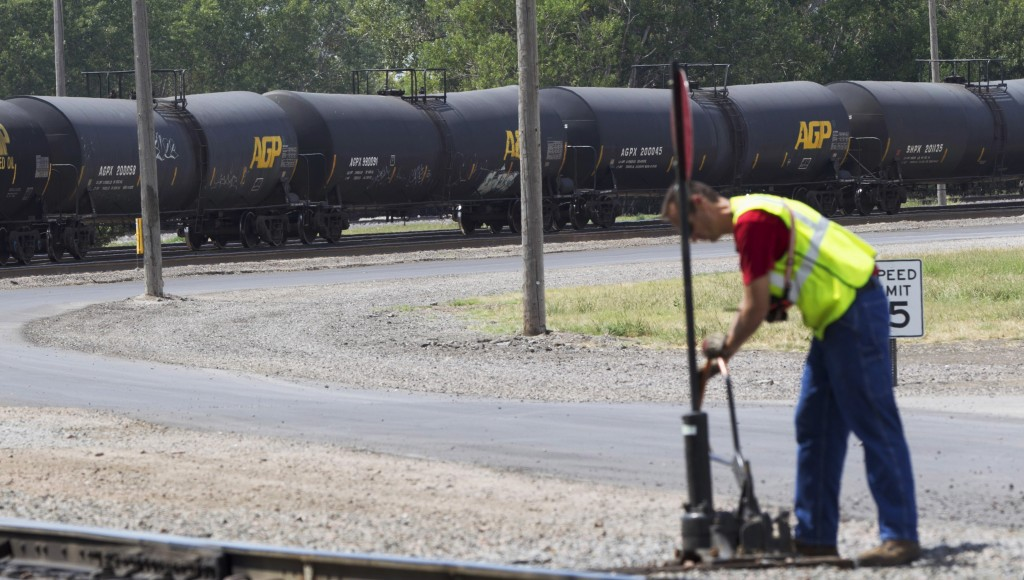 DOT-111 and AAR-211 class rail tankers pass by on the background as a man works at the Union Pacific rail yard in Council Bluffs, Iowa. (AP Photo/Nati Harnik, File)