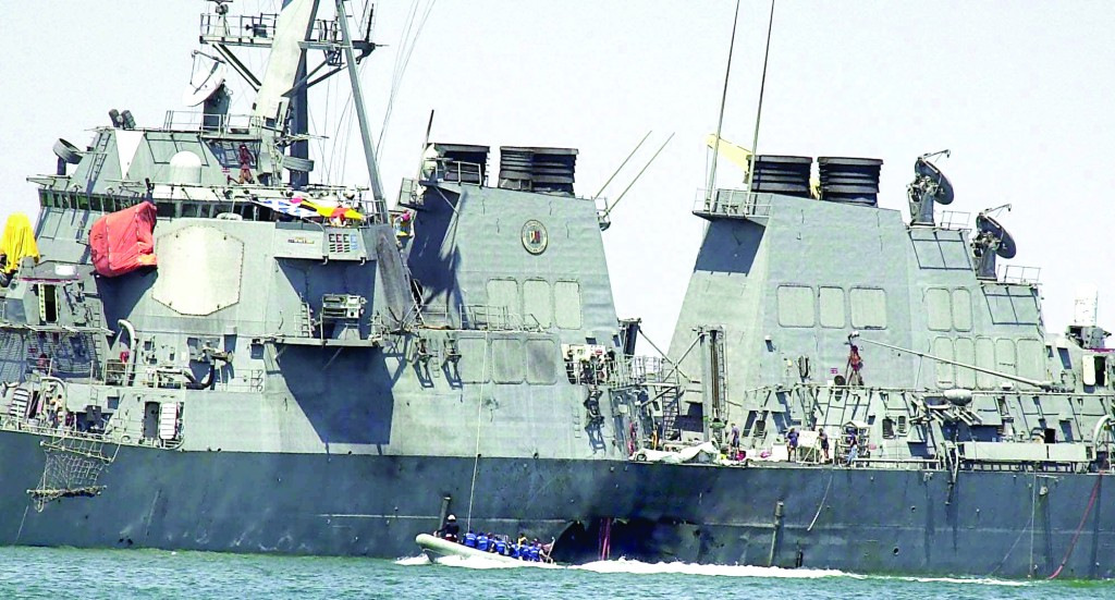 In this Sunday Oct. 15, 2000 file photo, investigators in a speed boat examine the hull of the USS Cole at the Yemeni port of Aden, after a powerful explosion ripped a hole in the U.S Navy destroyer, killing at least 17 sailors and injuring some 30 others. (AP Photo/Dimitri Messinis, File)