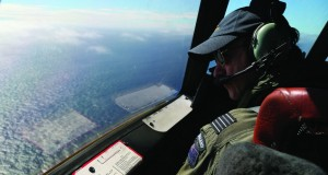 Royal New Zealand Air Force P-3 Orion's captain, Wing Commander. Rob Shearer watches out of the window of his aircraft while searching for the missing Malaysia Airlines Flight MH370 in the southern Indian Ocean, Monday, March 31, 2014. (AP Photo/Rob Griffith, Pool)