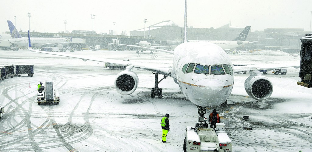 A United Airlines airplane is prepared to be pushed back from a gate at Newark Liberty International Airport in Newark NJ. during a recent snow storm. (AP Photo/Ted S. Warren)