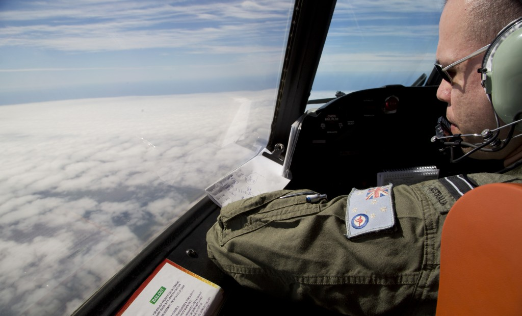 Flight Lt. Jayson Nichols looks out the cockpit of a Royal Australian Air Force AP-3C Orion aircraft during a search operation, Thursday. (AP Photo/Michael Martina, Pool)