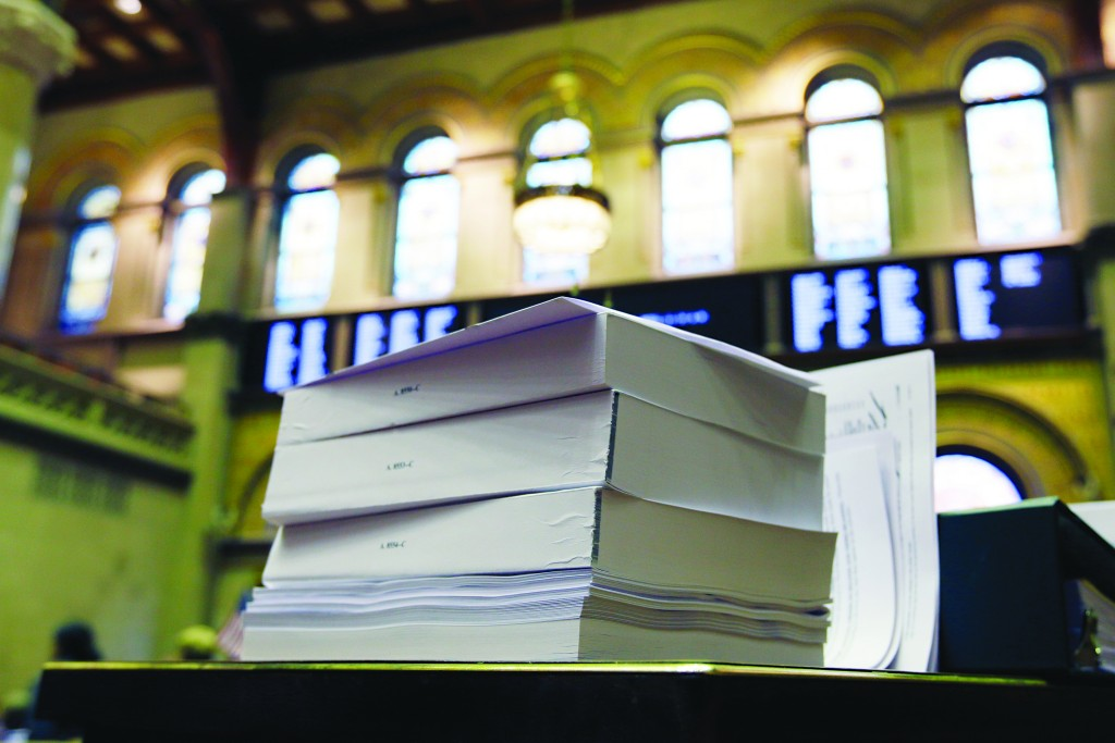 Budget bills on Wednesday sit on a desk in the Assembly Chamber. (AP Photo/Mike Groll)