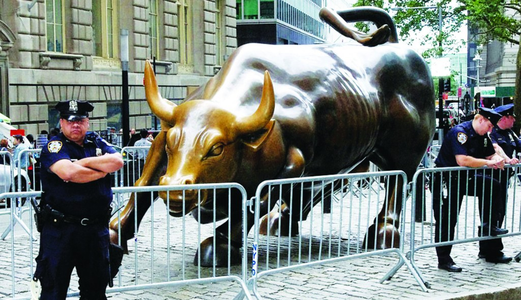 """Police officers stand near barricades surrounding """"Charging Bull,"""" the bronze sculpture that symbolizes Wall Street, in this 2011 photo taken during the Occupy Wall Street protests."""