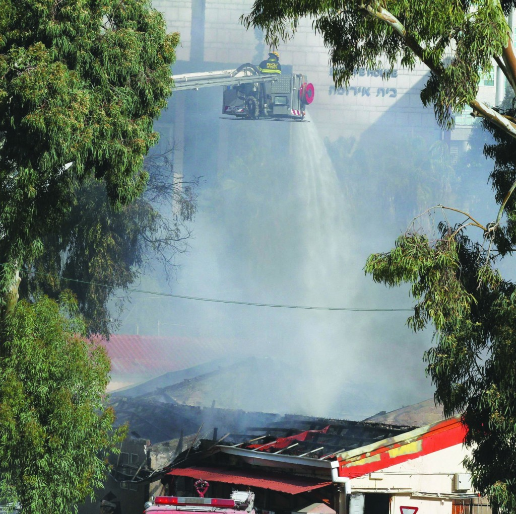 Firefighters extinguishing a blaze at the Defense Ministry headquarters in Tel Aviv on Wednesday.   (Roni Schutzer/FLASH90)