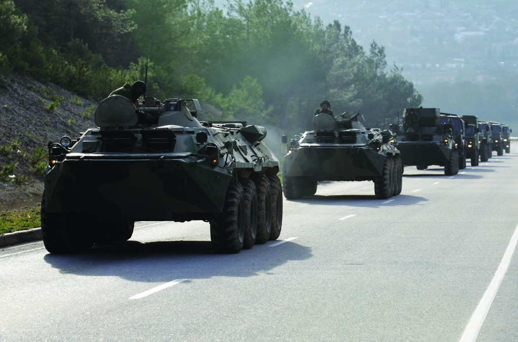 A convoy of military vehicles bearing no license plates travels on the road from Sevastopol to Simferopol, Crimea, Ukraine, Monday. (AP Photo/Darko Vojinovic)
