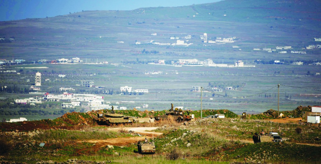 Israeli tanks are shown positioned near the site where Israeli troops shot two Hizbullah terrorists, in the Golan Heights on Wednesday. (REUTERS/Ronen Zvulun)